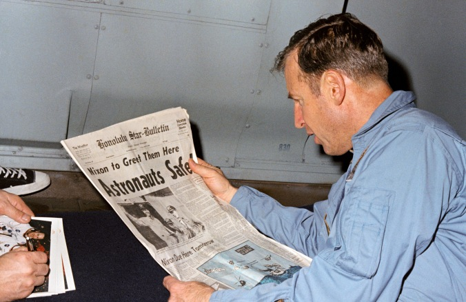 Lovell reads the newspaper front page shortle after he and his crewmates safely splashed down after the Apollo 13 mission.