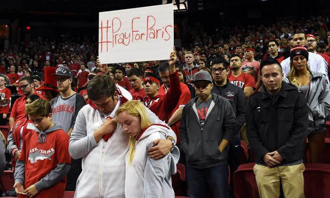 In this image made available by the Las Vegas News Bureau, UNLV fans observe a moment of silence for the victims of the terrorist attacks in Paris Friday, Nov. 13, 2015 before UNLV's basketball game against Cal Poly at the Thomas & Mack Center in Las Vegas. (Sam Morris/Las Vegas News Bureau via AP)